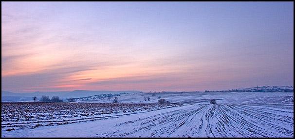 Un fine couche de neige recouvre les champs.